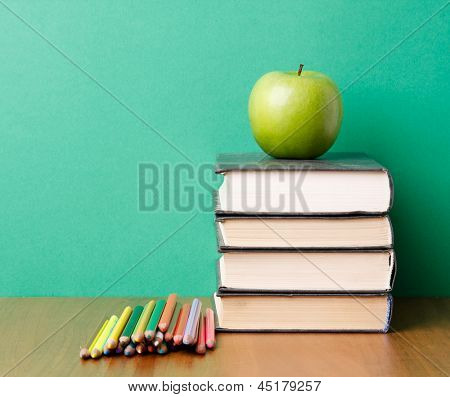 Green apple on a pile of books and pencils, isolated on green background