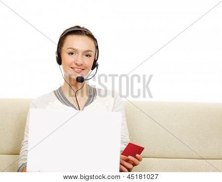 A woman working on a laptop, holding a red card