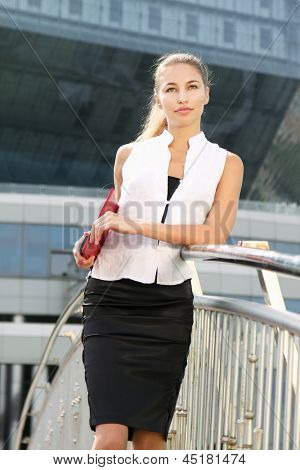Portrait of a young businesswoman standing near classic office buildings in a city, holding a folder