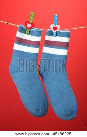 Colorful socks hanging on clothesline, on color background