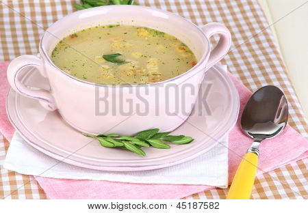 Nourishing soup in pink pan on wooden table close-up