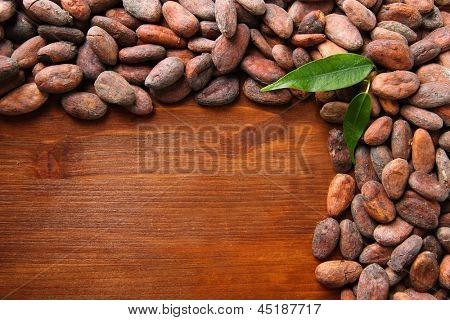 Cocoa beans with leaves on wooden background