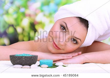 Beautiful young woman with towel on her head on bright background