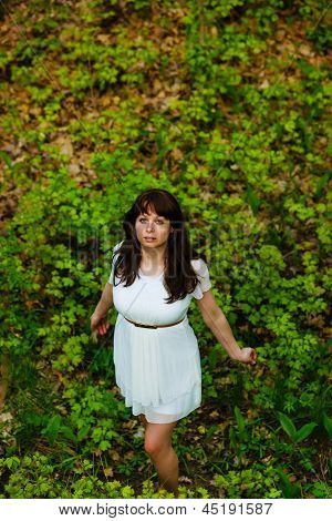 top view of young brunette woman in white dress standing on gree