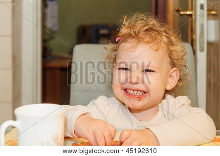 Little Girl With Dirty Facel Eating Cookie