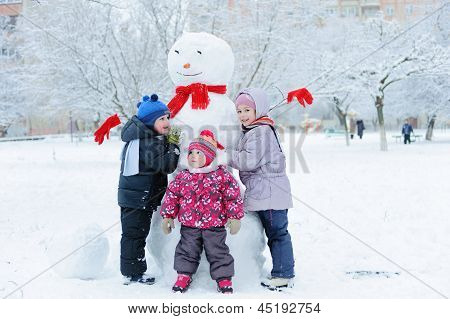 Children Building Snowman In Garden