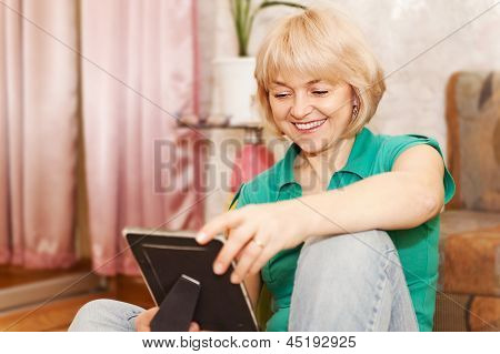 Mature Woman Looking At Photo At Home