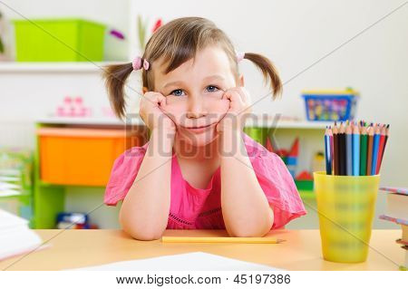 Upset Little Girl Sitting At Desk