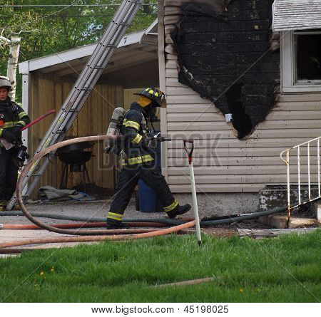 Firefighter Brings Water Hose to House Fire