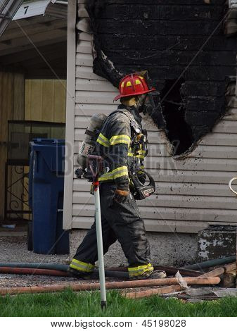 Firefighter Scans Damage at House Fire