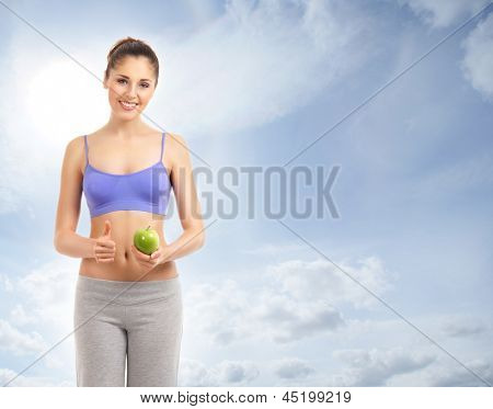 Young attractive sporty woman with a green apple over the heaven background