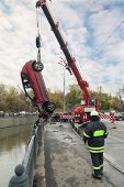 MOSCOW - OCT 9: Peugeot 206 suffered in the river Yauza and large red rescue vehicle helps injured i