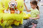Girl sits near to yellow dragon