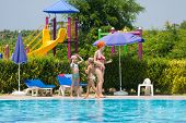 picture of inflatable slide  - Mother with children spend time around the pool - JPG