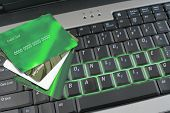 image of internet-banking  - glowing online banking on laptop keyboard with green credit and access cards - JPG