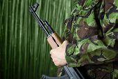 stock photo of ak-47  - Soldier holding rifle AK - JPG