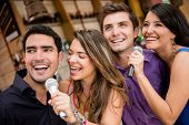 stock photo of karaoke  - Group of people karaoke singing at a bar having fun - JPG