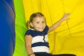 stock photo of bounce house  - Cute little Girl playing on inflatable Side - JPG
