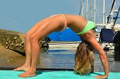 stock photo of dhanurasana  - Woman demonstrates yoga on a paddle board - JPG