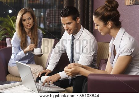 Young businesspeople working late on laptop computer sitting in hotel lobby or bar, drinking coffee.