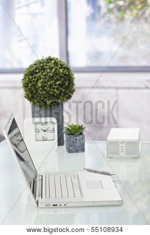Laptop placed on tidy desktop.