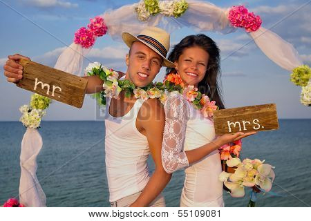 Groom with bride wearing lei, standing under archway on beach