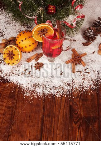 Glass of mulled wine and orange on a snowy table