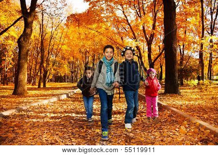Group Of Kids Go To School In Autumn Park