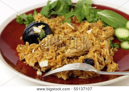 An authentic Saudi chicken kabsa (known in Qatar as majbous), garnished with raisins, parsley and almond flakes, on a serving bowl. Kabsa is a national staple for Saudi Arabia and the Arab Gulf States