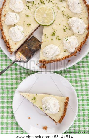 Traditional key lime pie decorated with whipped cream and lime zest on a dish