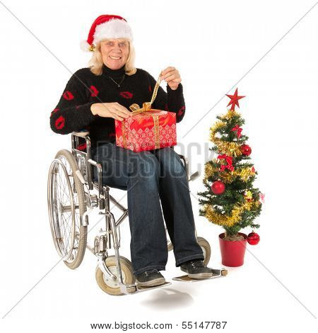 Chirstmas time with gifts and tree in wheelchair isolated over white background