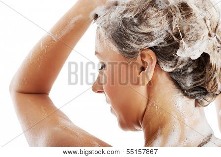 Beautiful woman taking a shower and shampooing her hair. Isolated on white.
