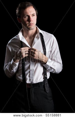 Attractive man unbuttoning shirt. Studio shot over black.