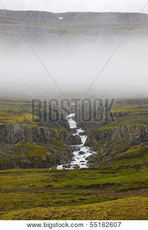Iceland. East Fiords. River And Rocks With Fog.