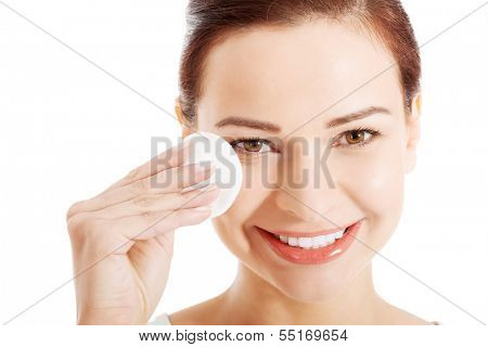beautiful woman cleaning her face with cotton pads. Isolated on white.