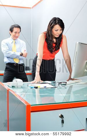 Asian Employee or secretary getting being sexually harassed by her boss or manager, he is looking her at the backside while she is working