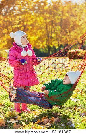 Little girl shakes hammock in wich little boy dozes