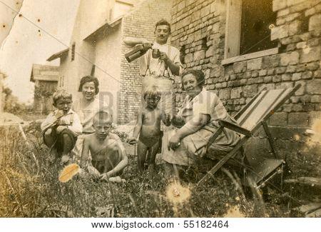 GANSERNDORF, AUSTRIA, CIRCA 1930s: Vintage photo of farmers family in front of their house, Ganserndorf, Austria, circa 1930s