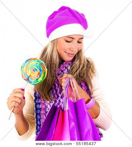 Portrait of cute woman with shopping bag and wearing Santa hat isolated on white background, holding in hands colorful lollipop, Christmastime concept