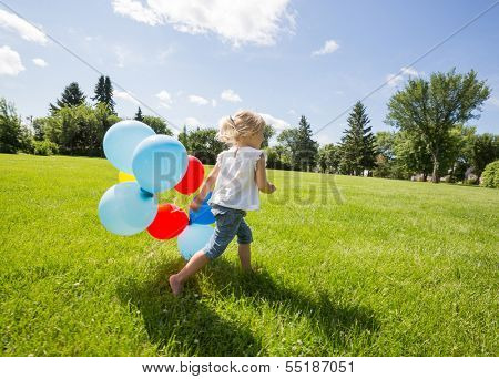 Full length of happy young girl with helium balloons running in grassy meadow