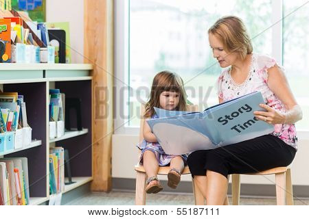 Mature female teacher with cute girl reading book in school library