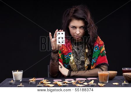 Attractive young fortune teller holdin card