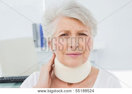 Portrait of a senior woman wearing cervical collar in the medical office