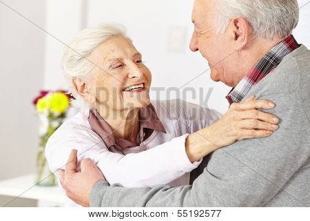 Two happy senior citizens dancing and smiling in a dancing class
