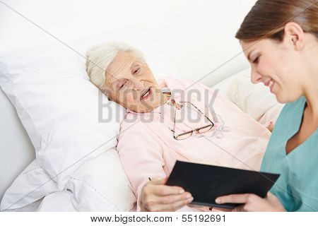 Geriatric nurse reading book to senior citizen woman in bed