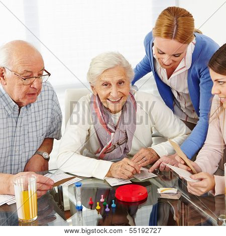Happy family with senior couple playing parlor games