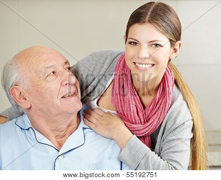 Smiling extended care assistant with happy senior citizen