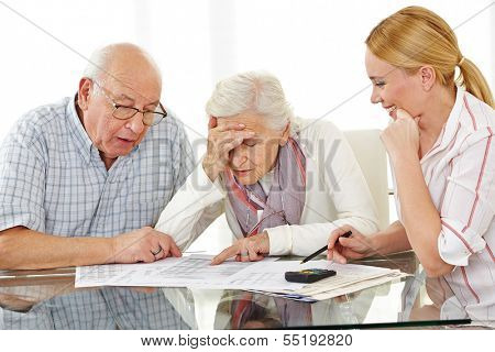 Senior couple with financial advisor looking shocked at bills