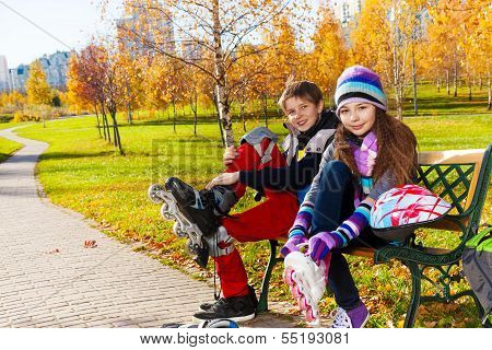 Two Kids Putting On Roller Blades