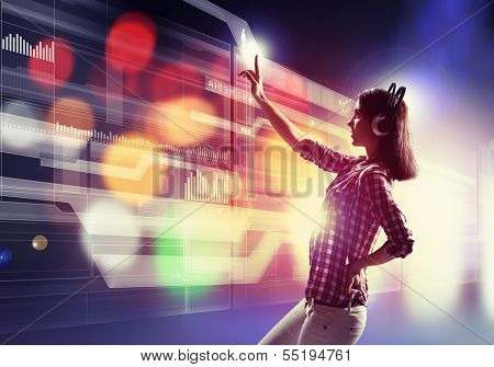 Image of young woman with headphones touching virtual screen